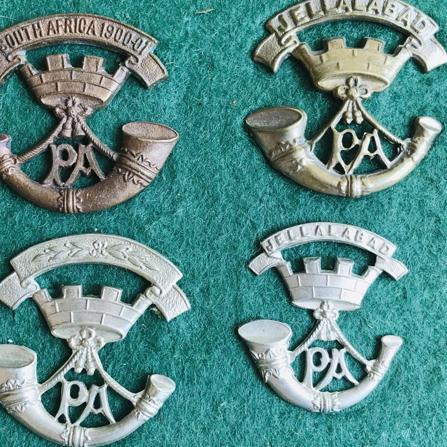 A collection of 12 Somerset light infantry cap badges